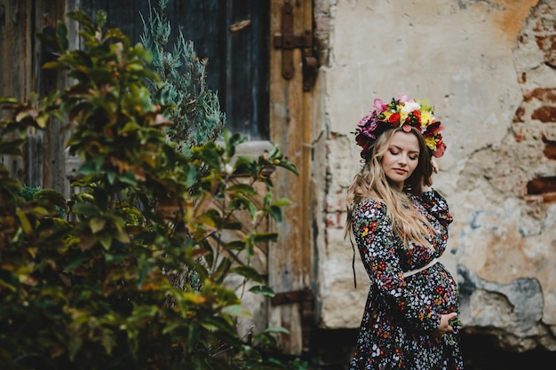 Weibliches porträt. entzückende schwangere frau in den blumenkranzhaltungen