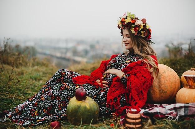 Weibliches porträt. reizend schwangere frau im langen kleid und im rot s