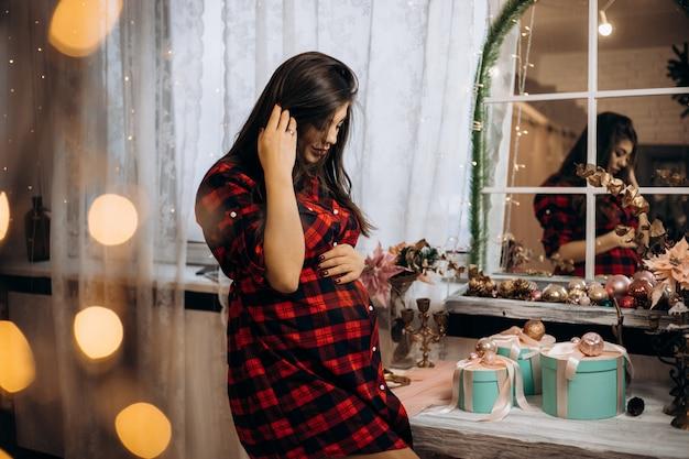 Weibliches portrait schwangere frau in überprüftem hemd wirft im gemütlichen raum mit weihnachtsbaum auf