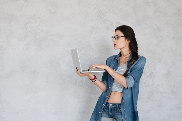 Weibliches profil, das auf laptop schreibt