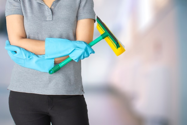 Weibliches reinigungspersonal im undeutlichen hintergrund des badezimmers