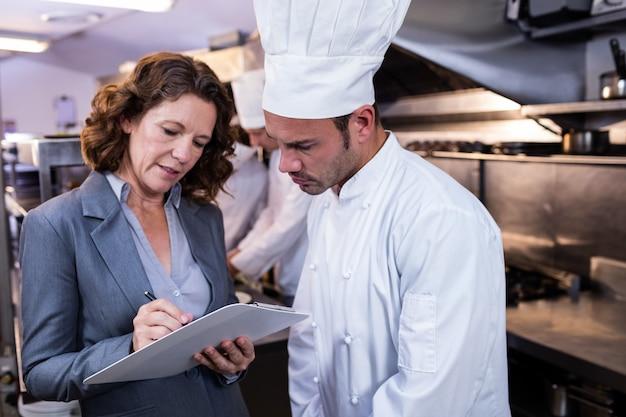 Weibliches restaurantmanagerschreiben auf klemmbrett bei der interaktion mit küchenchef