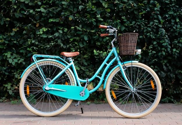 Weibliches retro-fahrrad mit korb auf grüner laubwand. aktives lifestyle-konzept.