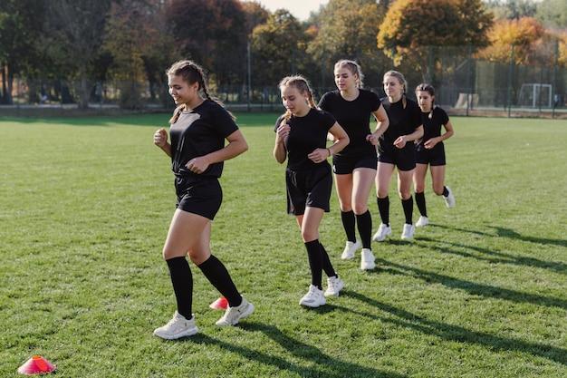 Weibliches rugbyteam, das durch kegel läuft