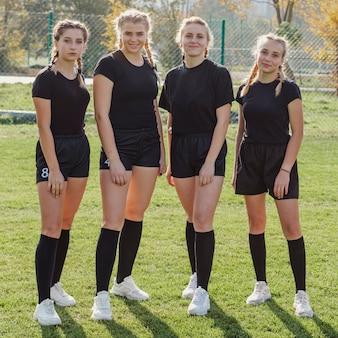 Weibliches rugbyteam, das fotografen betrachtet