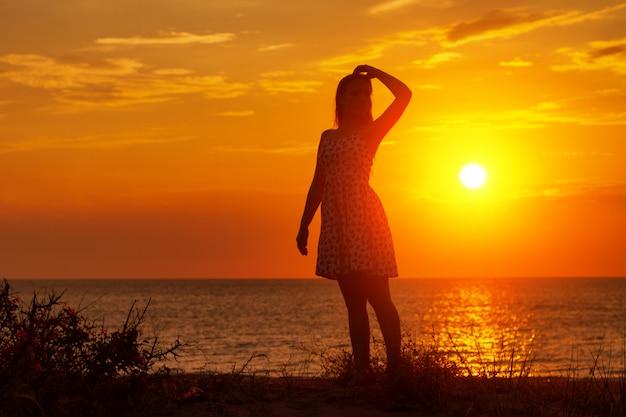 Weibliches schattenbild bei sonnenuntergang auf dem strand, hände oben