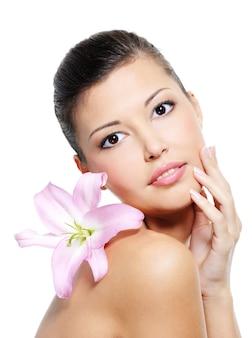 Weibliches schönheitsporträt mit einer lilie auf ihrer schulter auf weiß