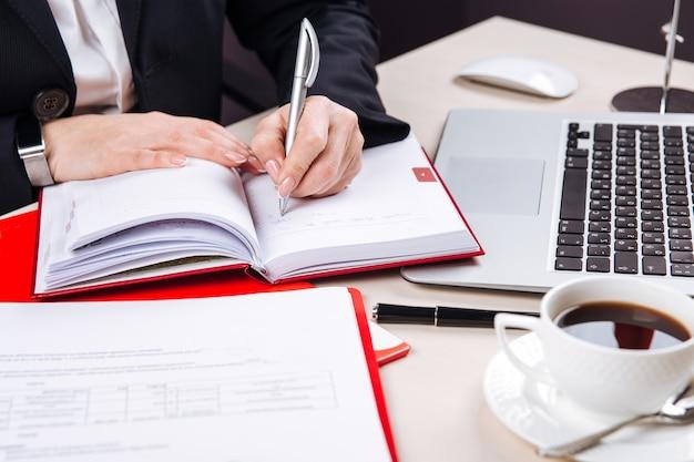 Weibliches schreiben im tagesplanerkaffee und im laptop