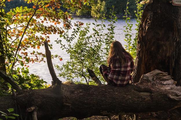 Weibliches sitzen auf baum, der die ansicht mit einem meer genießt
