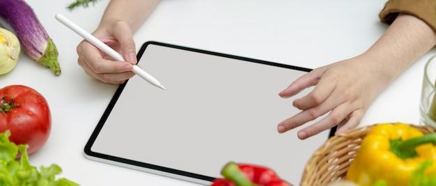 Weibliches suchmenü zum abendessen auf tablett mit leerem bildschirm auf weißem küchentisch mit frischem gemüse