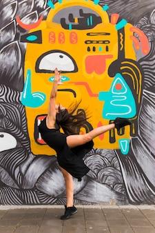 Weibliches tänzertanzen des hip-hops gegen graffitiwand
