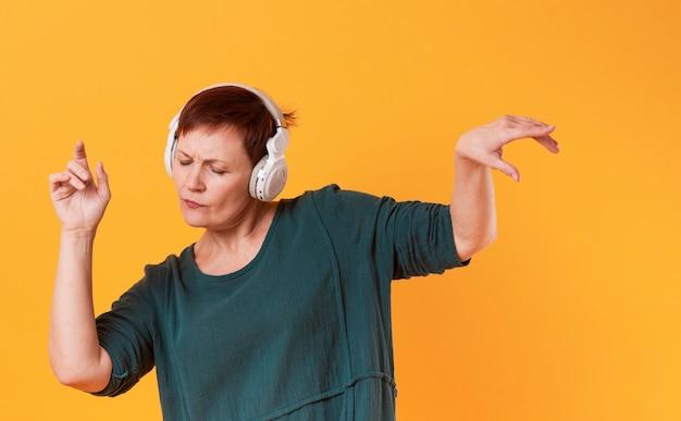 Weibliches tanzen des hippies und hörende musik
