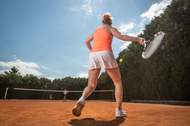Weibliches tennisspielertraining mit trainer auf dem sandplatz, sportkonzept