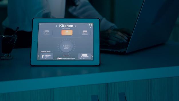 Weibliches tippen auf laptop, das von zu hause aus mit automatisierungsbeleuchtungssystem arbeitet, das sprachgesteuert auf dem tablett beim einschalten von glühbirnen verwendet wird. smart gadget reagiert auf befehle, frau mit automatisierter app-software