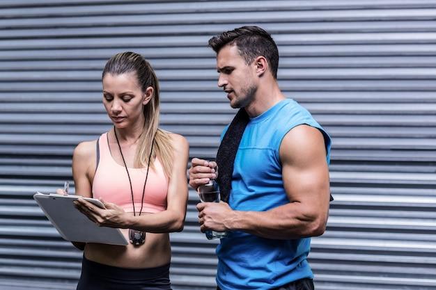 Weibliches trainerschreiben auf einem klemmbrett