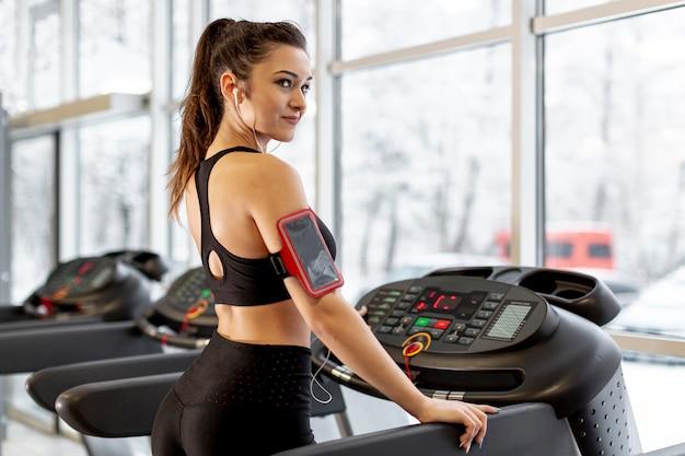Weibliches training der seitenansicht auf tretmühle