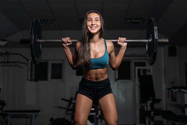 Weibliches training mit der langhantel, pumpende beine