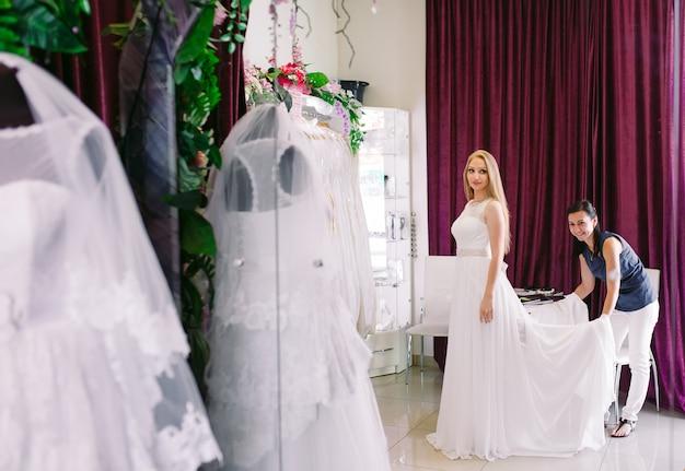 Weibliches versuchen auf hochzeitskleid in einem shop mit frauenassistent.