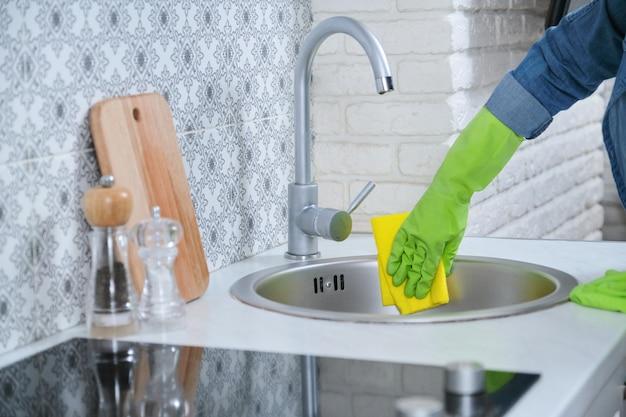 Weibliches waschen, das küchenwaschbecken und -mischer der reinigung poliert