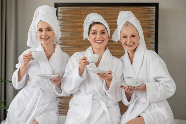 Weiblichkeit. erwachsene, fröhliche, schöne frauen in bademänteln und handtüchern auf dem kopf mit tassen, die sich ausruhen und zeit im spa verbringen