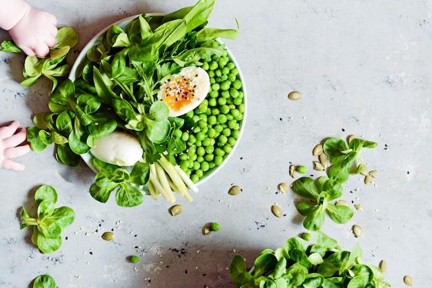 Weich gekochte eier mit salat, bärlauch, erbsen und petersilie.