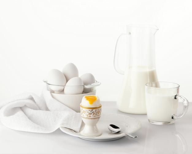 Weich gekochtes ei auf einem weißen teller mit goldenen und weißen ostereiern und milch. osterfrühstückskonzept.