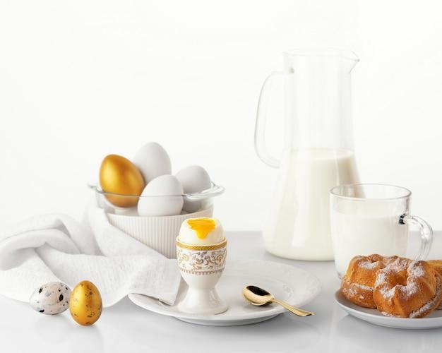 Weich gekochtes ei auf einem weißen teller mit goldenen und weißen ostereiern, wachteleiern, bäckerei und milch. osterfrühstückskonzept.