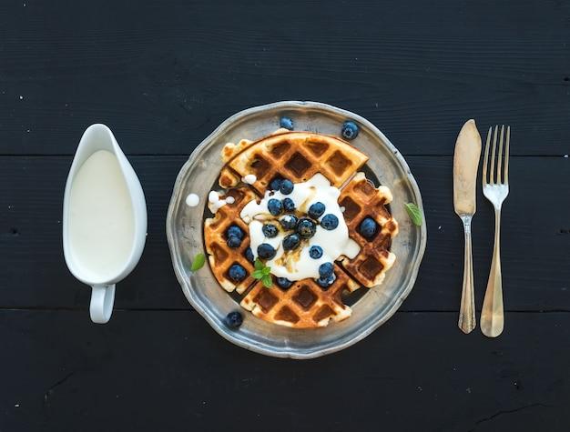 Weiche belgische waffeln mit blaubeeren, honig und schlagsahne auf weinlesemetallplatte