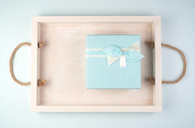 Weiche blaue geschenkbox mit einer schleife auf einem weißen tablett