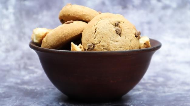 Weiche frisch gebackene kekse mit schokoladenstückchen in einer braunen steingutplatte auf grauem marmor. amerikanisches traditionelles süßes gebäck, köstliches hausgemachtes dessert. kulinarische hintergründe.