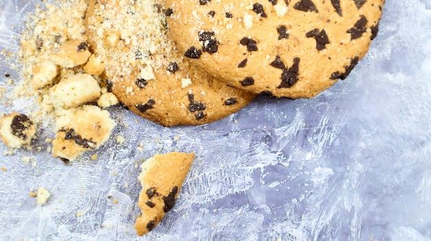 Weiche, frisch gebackene schokoladenkekse auf einer küchenarbeitsplatte aus grauem marmor. amerikanisches traditionelles süßes gebäck, köstliches hausgemachtes dessert. kulinarische hintergründe. flach liegen. platz kopieren.