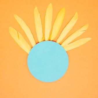 Weiche gelbe federn auf dem blauen rahmen des leeren kreises gegen einen orange hintergrund
