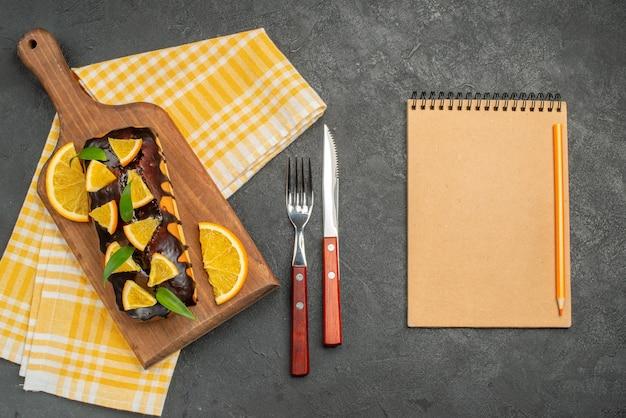 Weiche kuchen an bord und zitronen mit blättern auf grün gestreiftem handtuch neben dem notizbuch schneiden