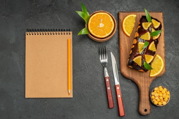 Weiche kuchen an bord und zitronen mit blättern und notizbuch auf dunklem tisch schneiden