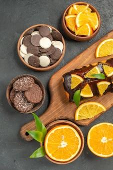 Weiche kuchen auf holzschneidebrett und orangen mit blattkeksen auf dunklem tisch schneiden