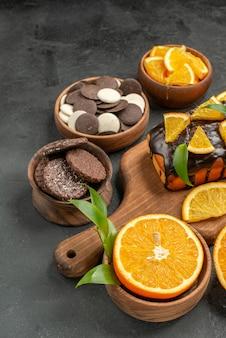 Weiche kuchen auf holzschneidebrett und orangen mit blattkeksen schneiden