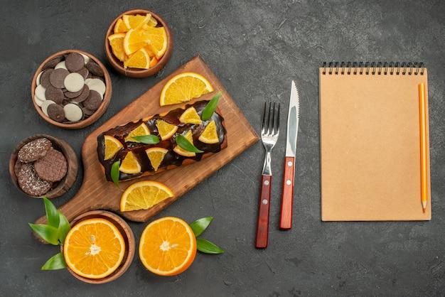Weiche kuchen auf holzschneidebrett und orangen mit blattkeksen und notizbuch schneiden