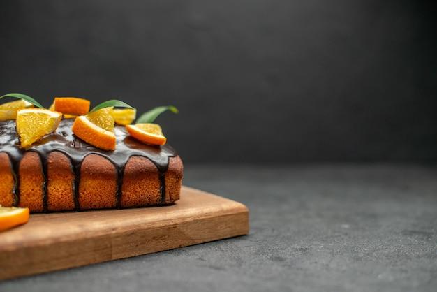 Weiche kuchen auf schneidebrett und orangen mit blättern auf dunklem tisch schneiden