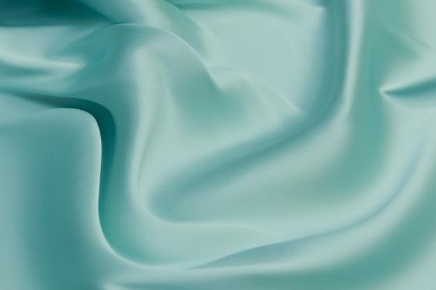 Weiche seidenstoff- oder satinstoffstruktur. faltiges stoffmuster. tidewater green ist ein 2021-farbtrend.
