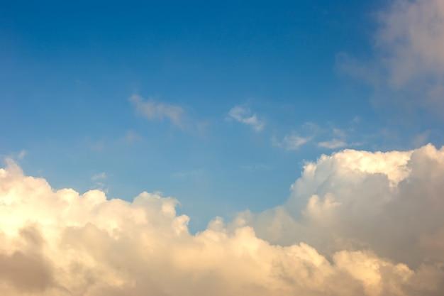 Weiche und zarte, weiße und gelbe wolken gegen den blauen himmel am unteren rand des rahmens.