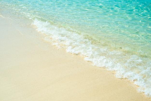 Weiche welle von blauem ozean auf sandigem strand.