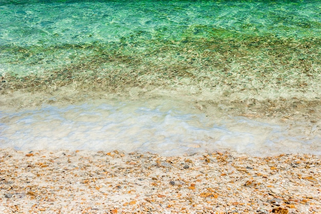 Weiche wellen mit wasserschaum auf kieselsteinen und sandstrand.