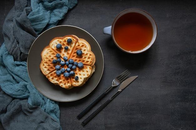 Weiche wiener waffeln mit blaubeeren und einer tasse tee