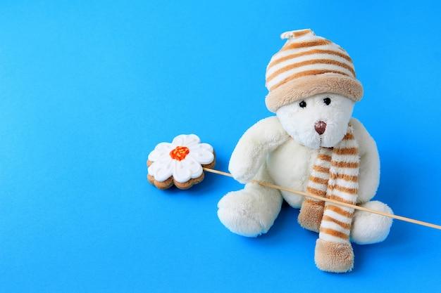 Weicher bär des spielzeugs hält in seinem tatzenlebkuchen auf einem stock auf einem blauen pfef das konzept eines feiertags und der glückwünsche