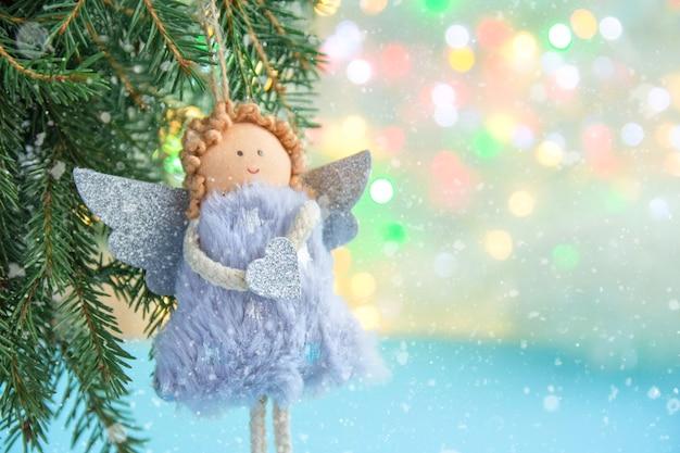 Weicher engel mit flügeln auf einem weihnachtsbaum auf einem hellen bokehhintergrund