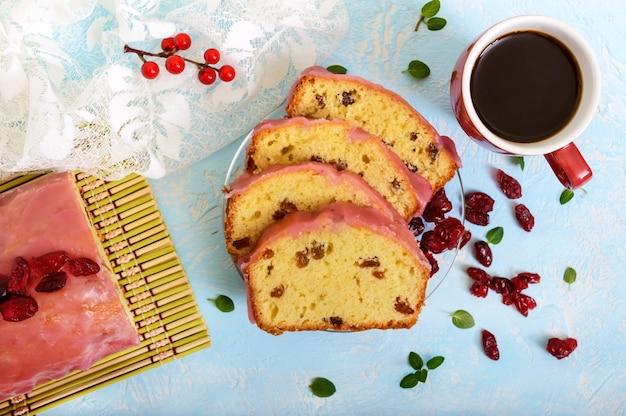 Weicher festlicher obstkuchen mit rosinen und getrockneten preiselbeeren und einer tasse kaffee