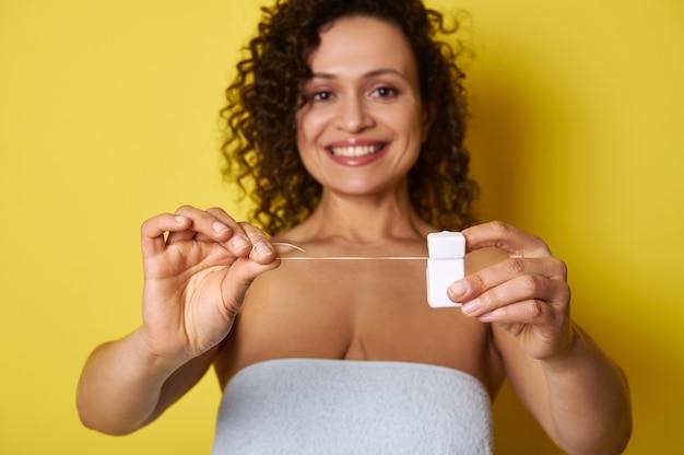 Weicher fokus auf hygiene-zahnseide in den händen der lächelnden frau mit dem schönen zahnigen lächeln, lokalisiert