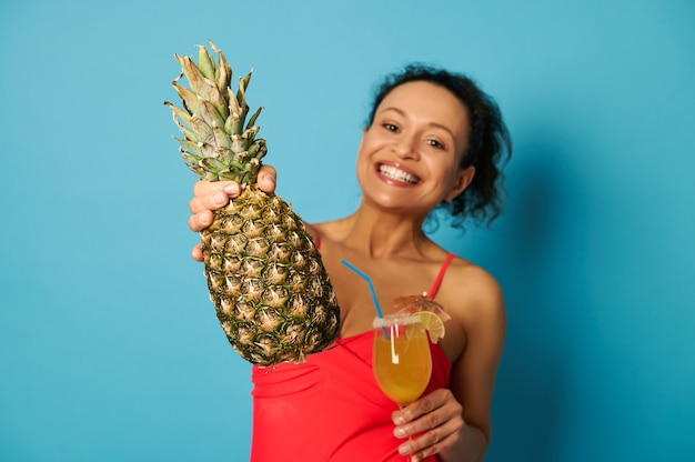 Weicher fokus auf leckere ananas in der hand einer attraktiven lächelnden frau im roten badeanzug mit einem glas cocktail in der hand.