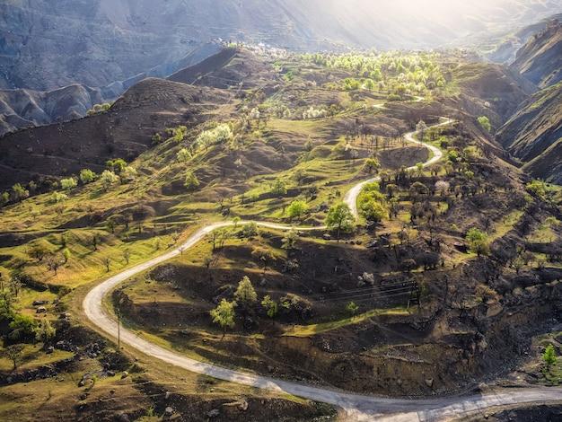 Weicher fokus. bergserpentin im morgensonnenlicht. eine schmale unbefestigte bergstraße durch die hügel zu einem hochgelegenen dorf. luftaufnahme.