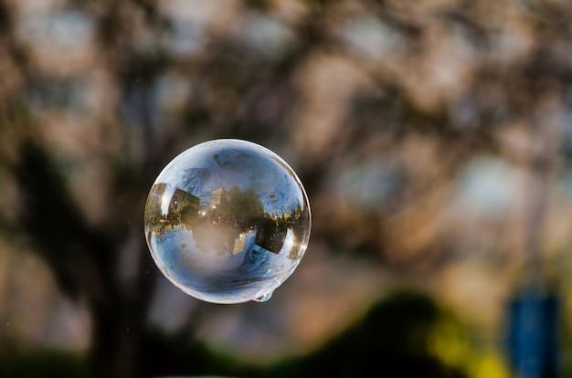 Weicher fokus einer blase mit reflexion von stadtgebäuden und bäumen darauf